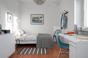 Image of a Scandinavian inpired bedroom. The walls are white with wooden floor boards. The bed is dressed in white linen with a black and white throw and grey and white striped rug on the floor. Ther eis a white desk to the right with a blue chair