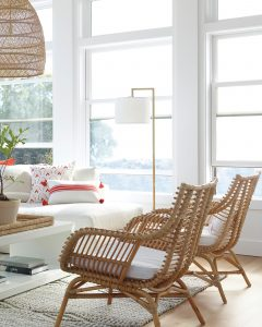 Image of a living room with two rattan chairs with white seat pads in the foreground.