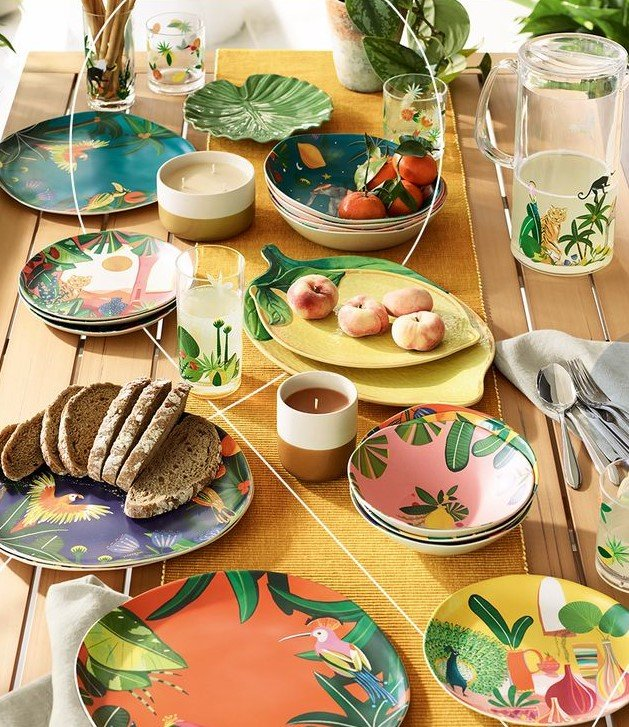 Image of an outdoor dining table dressed with a selection of colourful jungle themed tableware and glassware