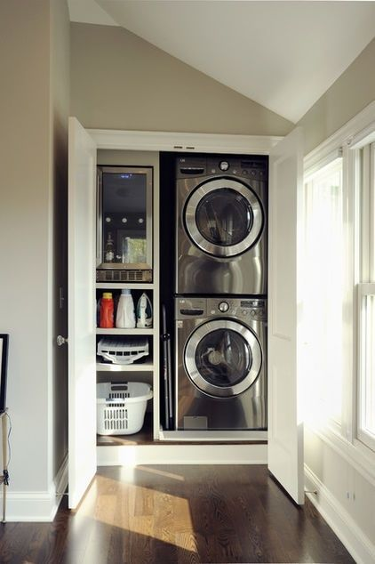 Image of a full height cupboard an an alcove of a kitchen or utility room. The doors are open. To the right hand side are a washing machine and tumble dryer stacked on top of each other with shelves to the left