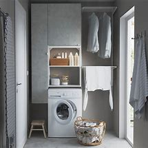 Image of the end wall of a utility room. There is a washing machine with cupboards built in to one side and above and hanging rails to the other side