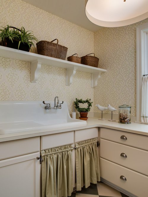 Image of the corner of a utility room. There is a pretty floral wallpaper with a white painted shelf on one wall with a row of woven baskets on it. The are fitted floor cabinets and the under sink area is hidden by decorative linen curtains. There are a couple of ornaments on the counter top