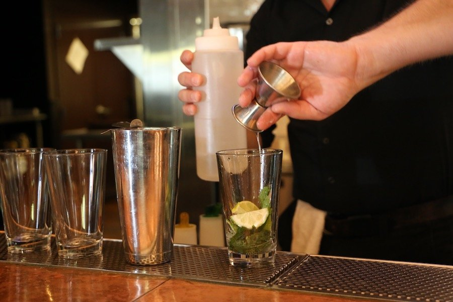 Image of a person mixing cocktails. It includes a glass, cocktail shaker and measure. The person is holding a bottle and puring from the measure into the glass.