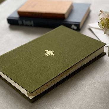 Image of a address book with a green cover embossed with a gold bee