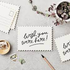 """Image of a table with a post showing the words """"wish you were here"""""""