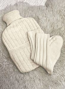 Image of a cream knitted cashmere hot water cover with matching socks on a grey sheepskin