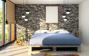 Image of a bed positioned against a brick wall. The base has a pallet like appearance. The bed is dressed with a  pale blue duvet. Either side of the bed a cluster of three pendant lights hangs from the ceiling