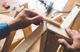 Image of a person assembling flat pack furniture showing only their hands